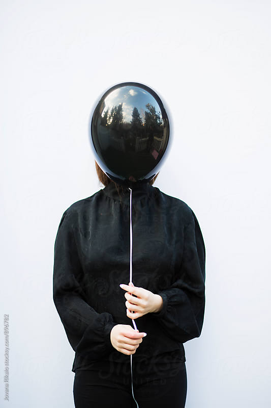 Portrait of a young woman holding black balloon in front of her face by Jovana Rikalo for Stocksy United