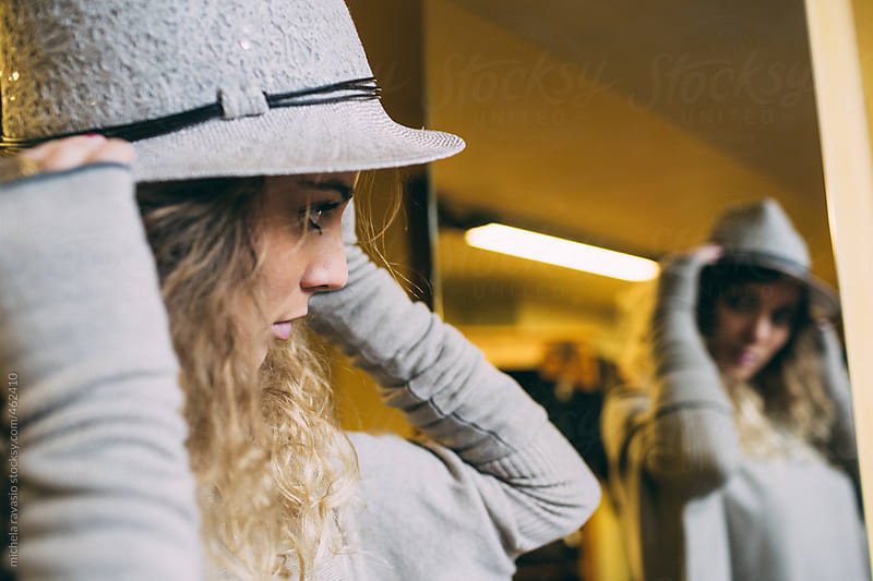Young woman trying on a hat in front of the mirror by michela ravasio for Stocksy United