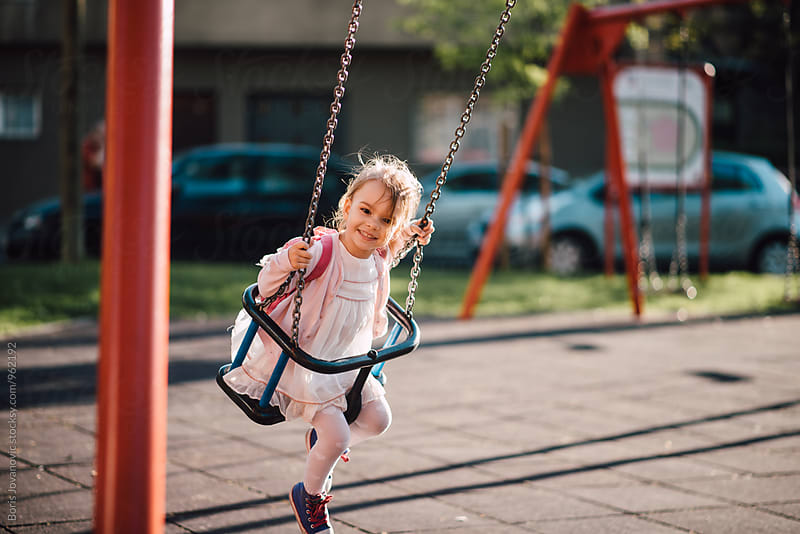 Young girl swinging in the outdoor playground by Boris Jovanovic for Stocksy United