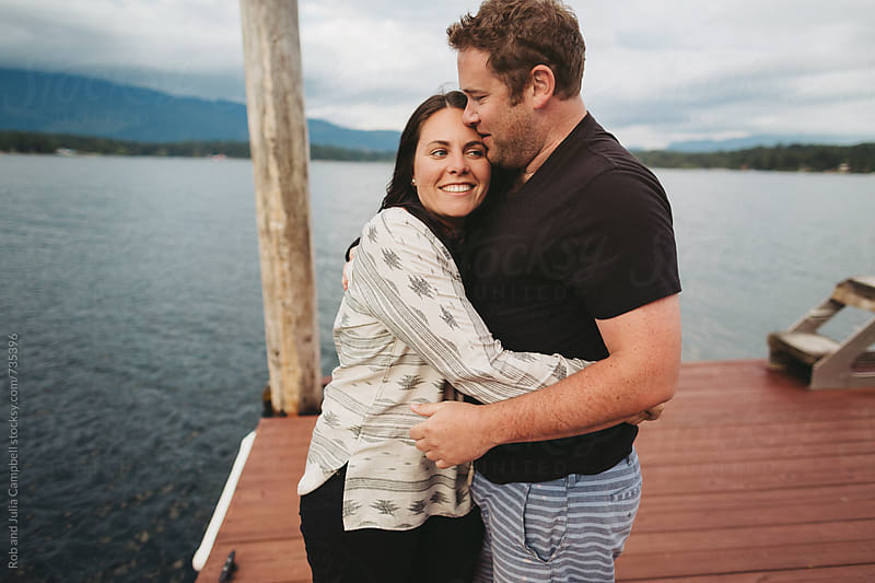 Young playful couple together on dock at lake hugging by Rob and Julia Campbell for Stocksy United