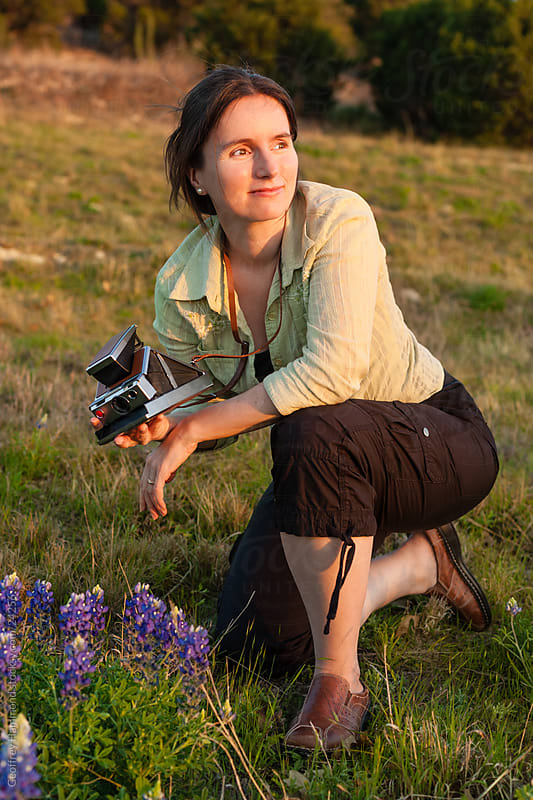 Woman with Camera and Bluebonnets Watching Sunset by Geoffrey Hammond for Stocksy United