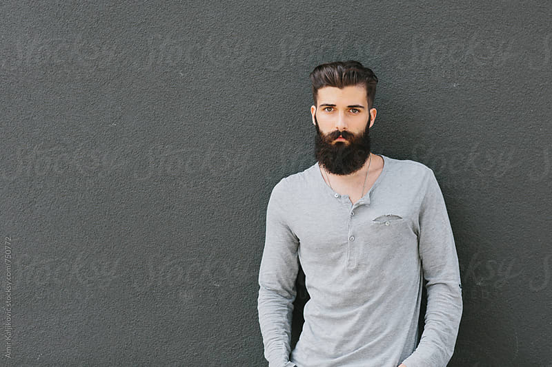 Cool young man standing in front of a gray wall by Amir Kaljikovic for Stocksy United