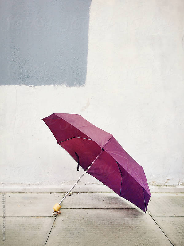 An open umbrella left on a pavement by a wall by James Ross for Stocksy United