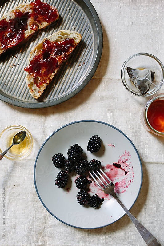 Breakfast of toast & jam, tea, and blackberries by Christine Han for Stocksy United
