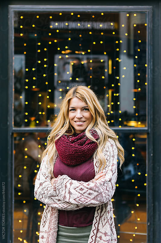 Cute Blonde Young Woman Posing Besides a Shop Window by VICTOR TORRES for Stocksy United