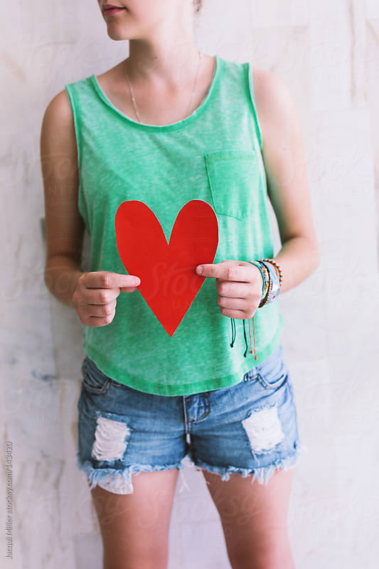 Teen girl holds a red paper heart in front of her body by Jacqui Miller for Stocksy United
