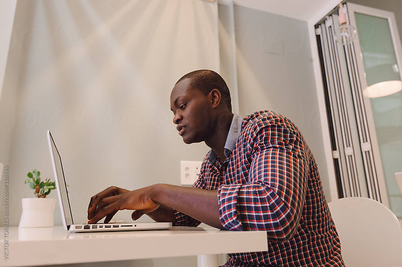 Black Man with a Laptop on a Wooden Table by VICTOR TORRES for Stocksy United