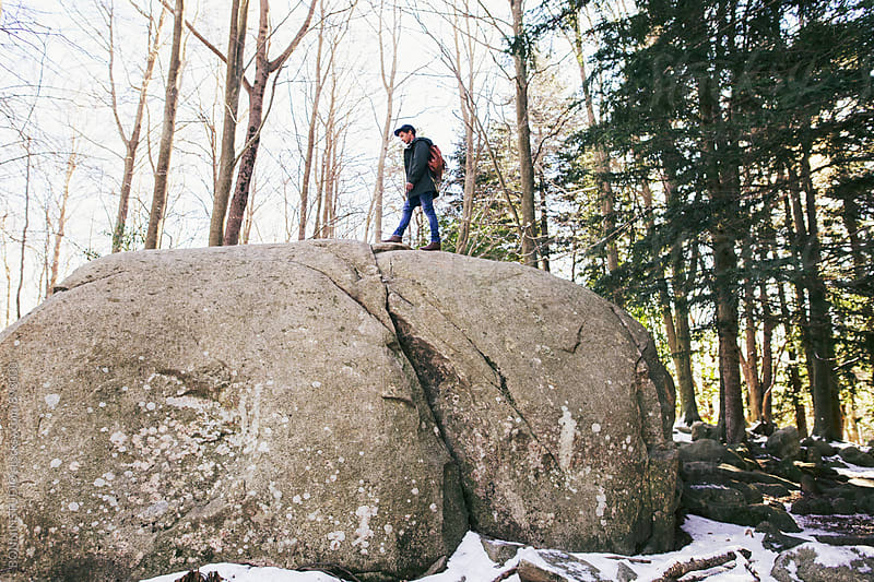 Mountaineer climbing on a big rock in the woods. by BONNINSTUDIO for Stocksy United