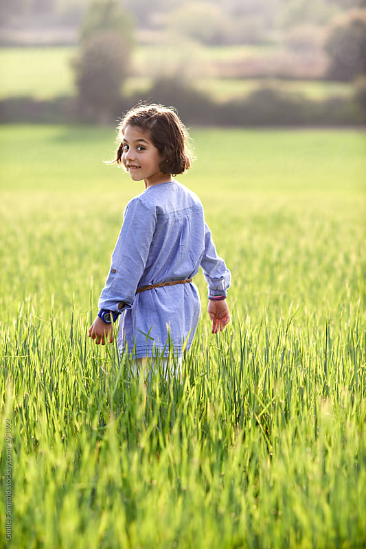 Little girl walking in a meadow at spring time. From behind by Guille Faingold for Stocksy United