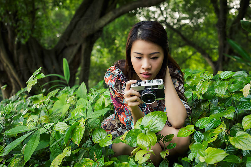 Young Asian woman with a mirrorless camera by Felix Hug for Stocksy United