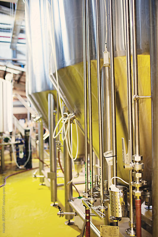 view along the side of large tanks, vats for brewing beer by Natalie JEFFCOTT for Stocksy United