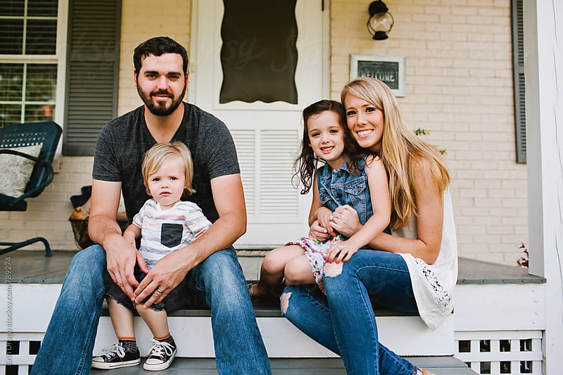 Family sitting on porch by Erin Drago for Stocksy United