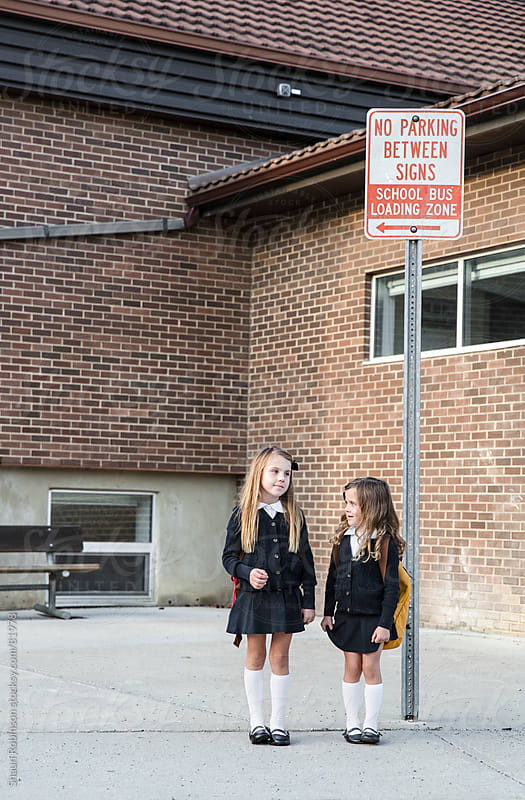 two girls waiting at a school bus stop outside a school by Shaun Robinson for Stocksy United