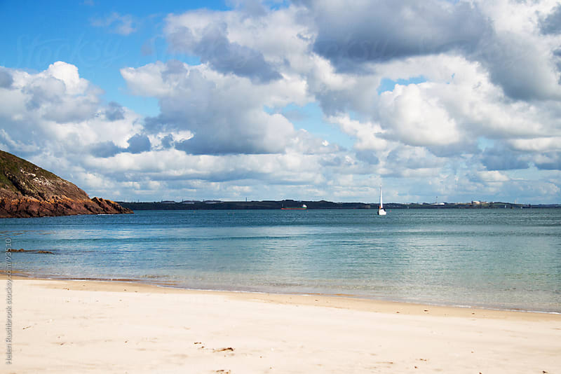 A yacht sailing towards an idyllic beach by Helen Rushbrook for Stocksy United