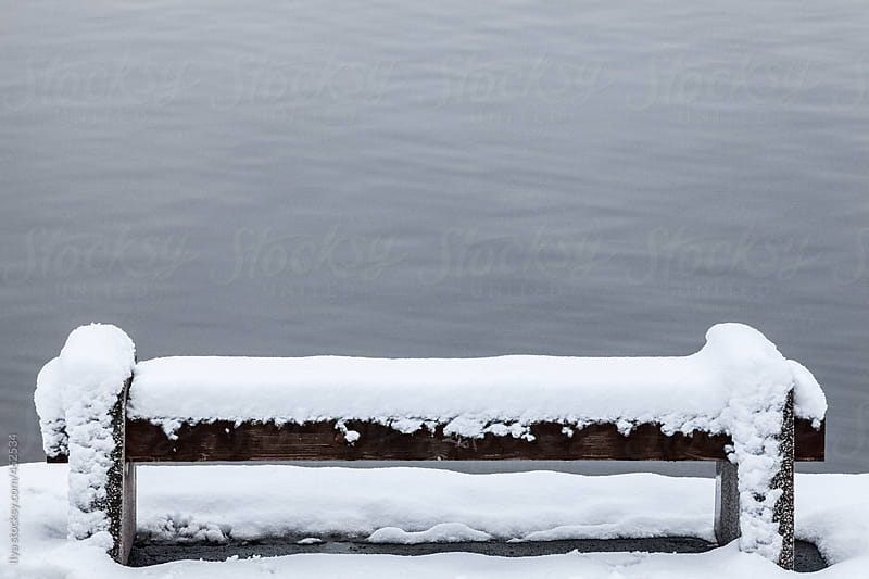 Snowy park bench on the lake shore by Ilya for Stocksy United