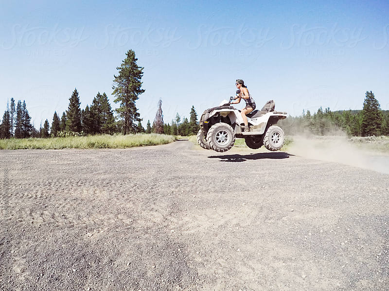 Woman Jumping ATV with Dirt Trails by MEGHAN PINSONNEAULT for Stocksy United