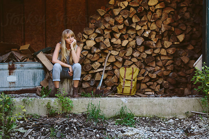 Young Woman Sitting In Front Of Stacked Chopped Wood by Laura Austin for Stocksy United