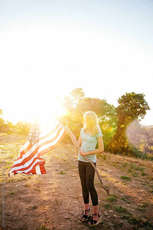 young girl holding USA flag by Rebecca Rockwood for Stocksy United