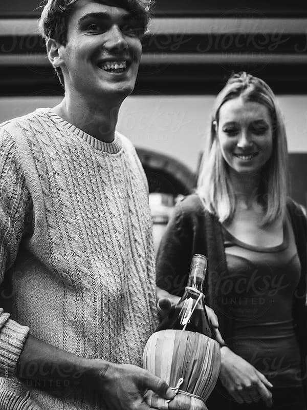 Happy couple holding a wicker wine bottle by Juri Pozzi for Stocksy United