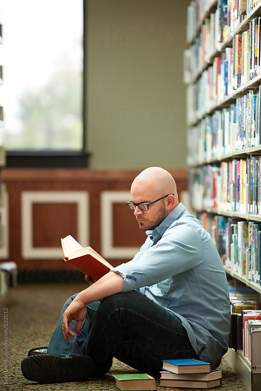 Library: Man Sitting in Aisle Reading by Sean Locke for Stocksy United
