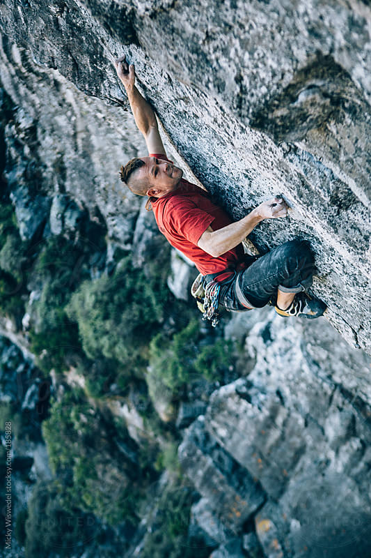 Rock climber on and overhanging rock face on Table Mountain by Micky Wiswedel for Stocksy United
