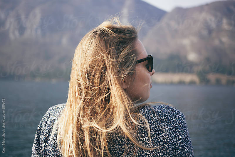 Good looking girl with sunglasses sitting at a lake. by Koen Meershoek for Stocksy United