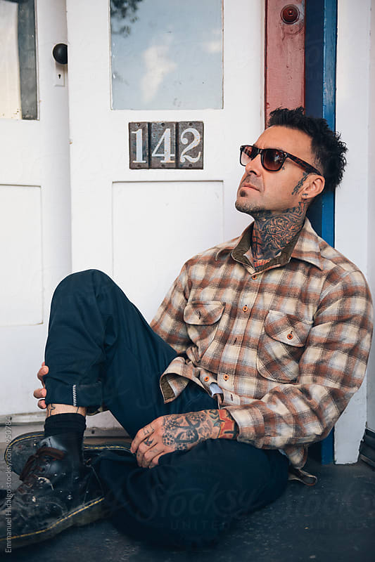 Tattooed male hanging out and sitting in front of doorway by Emmanuel Hidalgo for Stocksy United