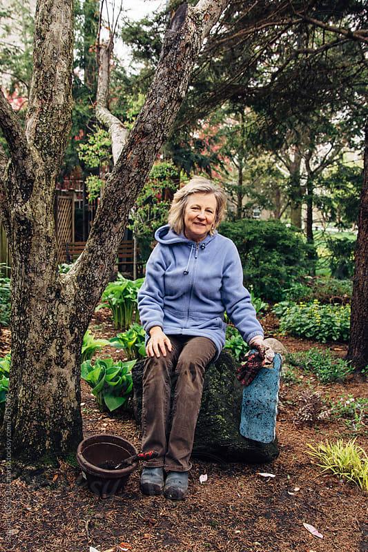 Senior gardening woman resting on a stone by Gabriel (Gabi) Bucataru for Stocksy United