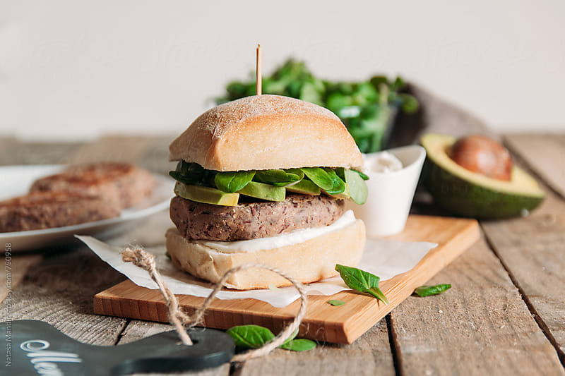 Burger made of sweet potatoes and black beans with avocado and salad by Nataša Mandić for Stocksy United