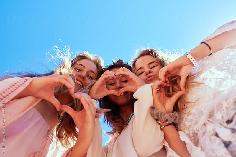 Three happy girls showing heart with hands by Guille Faingold for Stocksy United
