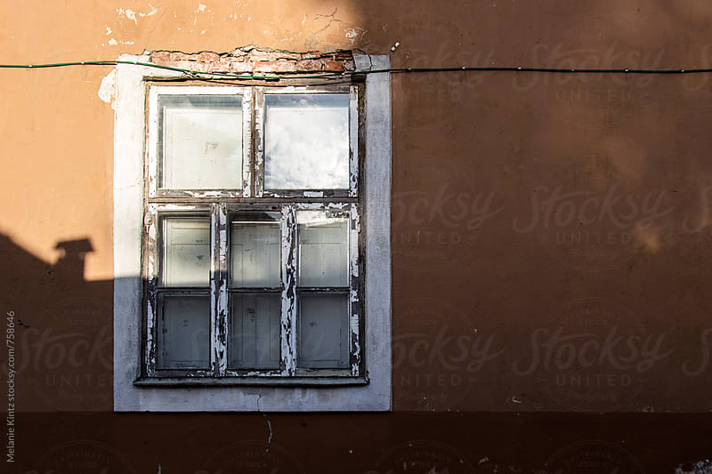 Old window in a damaged home by Melanie Kintz for Stocksy United