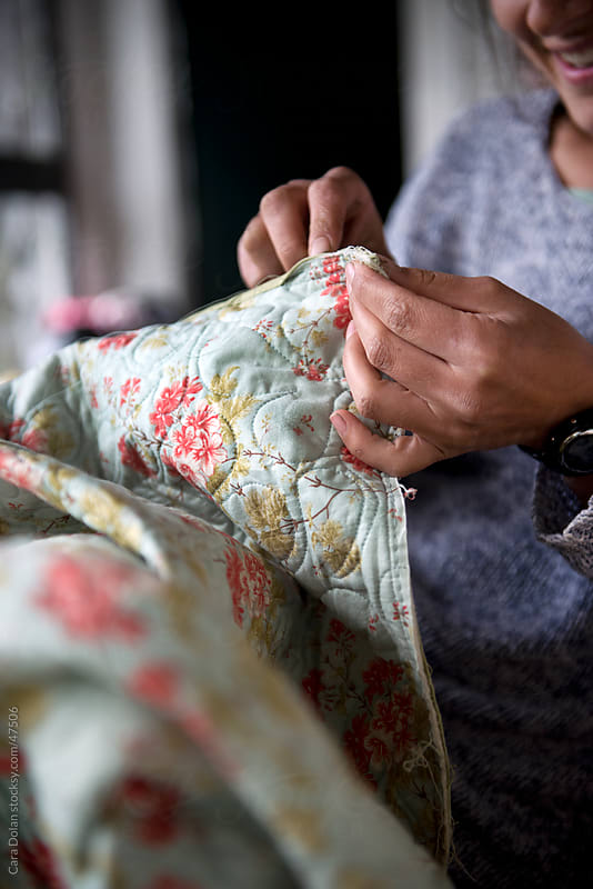 Woman sews a quilt by hand by Cara Dolan for Stocksy United