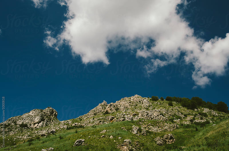 Clouds on sky over mountain in summer by Cosma Andrei for Stocksy United