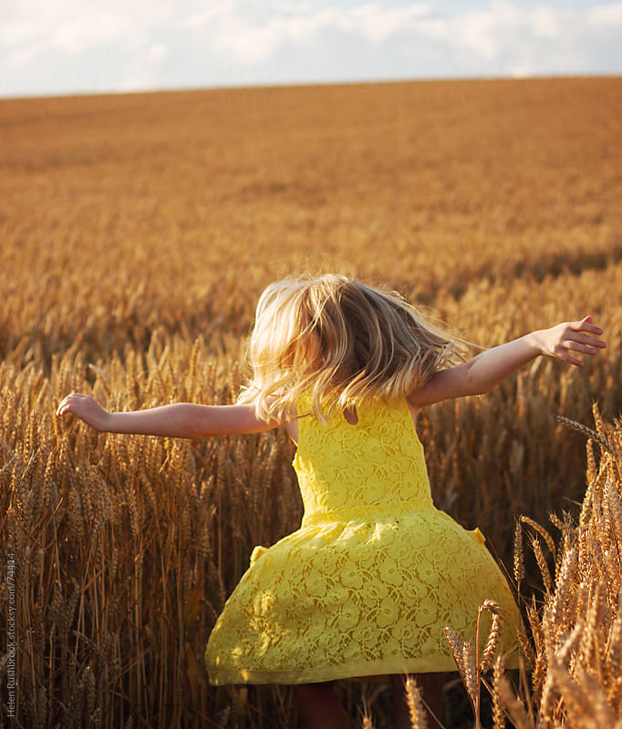 A little girl dancing in a field of wheat by Helen Rushbrook for Stocksy United