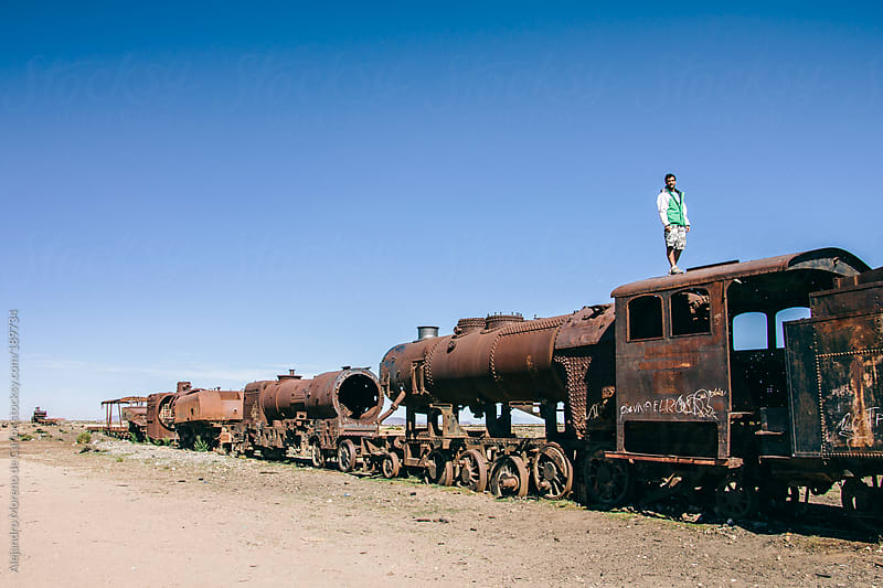 Young man on top of old abandoned rusty train by Alejandro Moreno de Carlos for Stocksy United