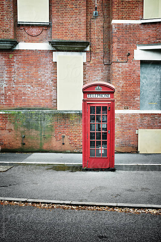 A telephone box beside an empty building by James Ross for Stocksy United