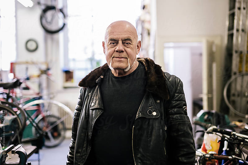 Portrait of Senior adult in Bicycle workshop by VegterFoto for Stocksy United