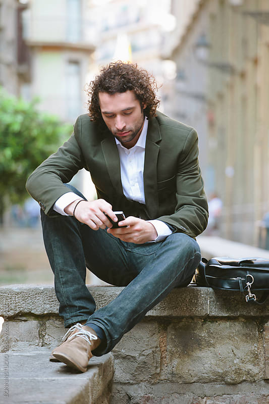 Young modern businessman writing with mobile phone sitting on Barcelona street. El gotic. by BONNINSTUDIO for Stocksy United