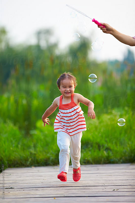 little asian girl playing with bubble outdoor by Bo Bo for Stocksy United
