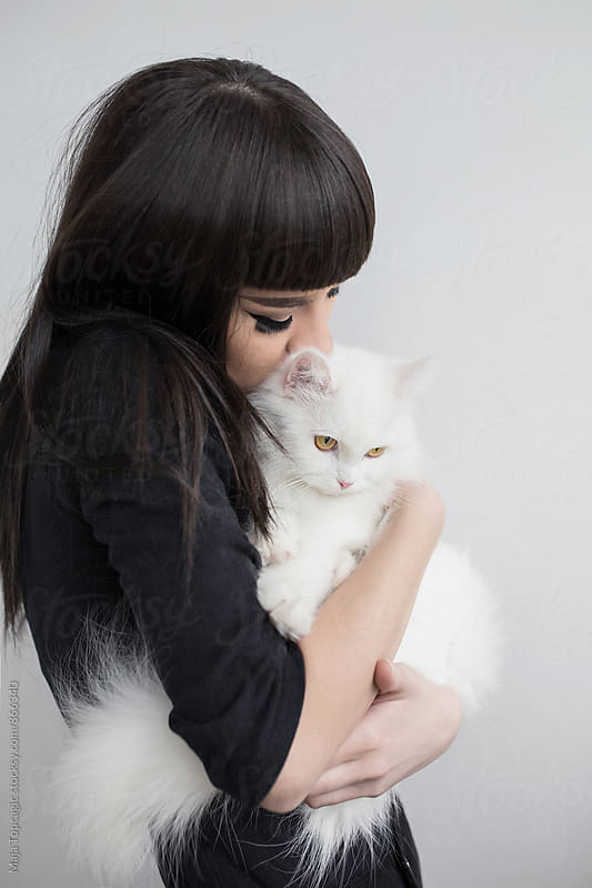 Young woman holding beautiful persian cat by Maja Topcagic for Stocksy United