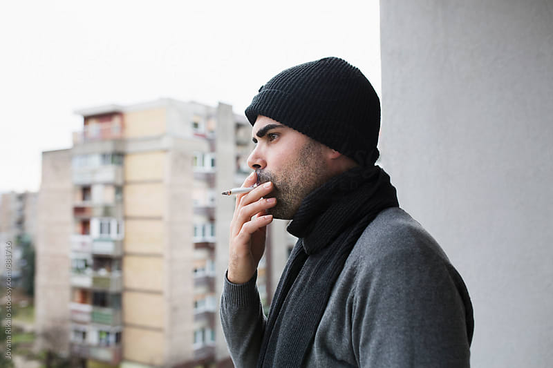 Portrait of a handsome man smoking on a terrace by Jovana Rikalo for Stocksy United