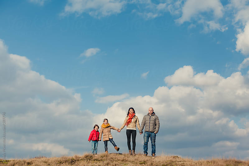 Portrait of a family of four under a big blue sky on a beautiful winter day by Cindy Prins for Stocksy United