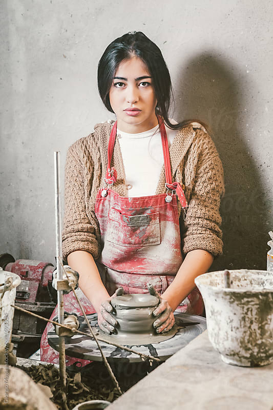 Young Woman Crafting Ceramics on a Pottery Wheel by Giorgio Magini for Stocksy United