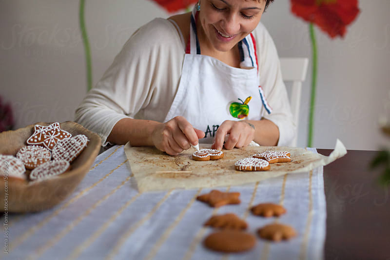 Woman decorates cookies in her kitchen by Jelena Jojic Tomic for Stocksy United