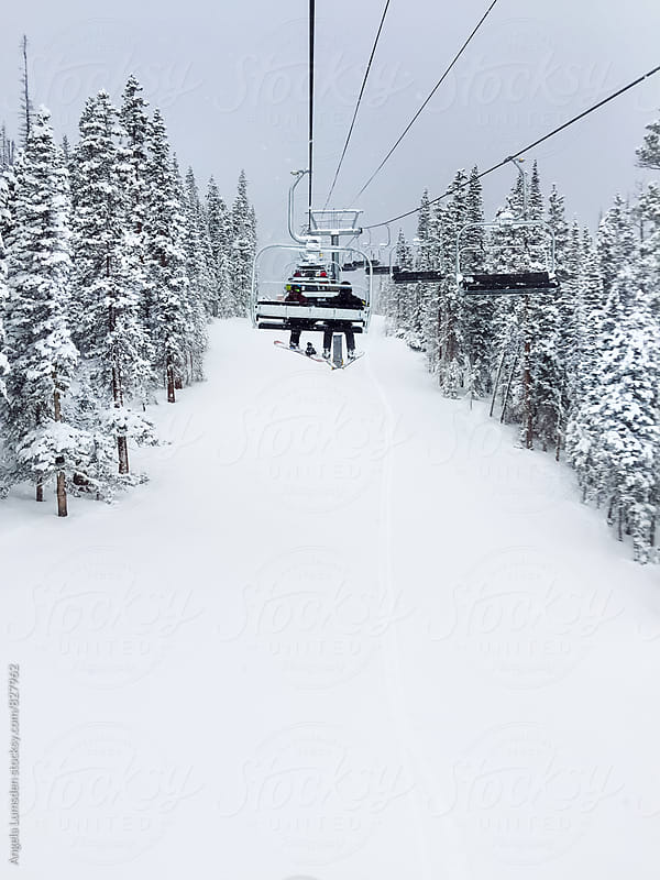 Skiers ride a chair lift between snow covered trees on a snow day by Angela Lumsden for Stocksy United