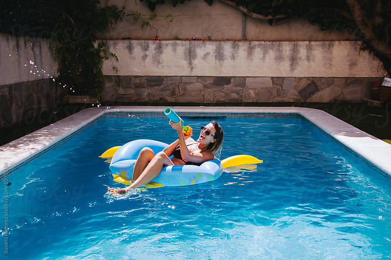 Woman sitting on a mattress in the pool, with water gun by Susana Ramírez for Stocksy United