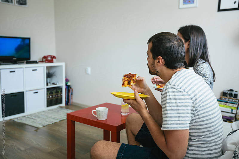 Young couple eating pizza by Aleksandar Novoselski for Stocksy United