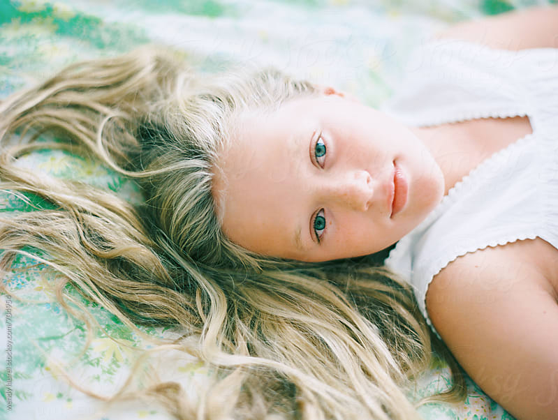 portrait of blonde girl wtih hair spread out on vintage floral sheets by wendy laurel for Stocksy United