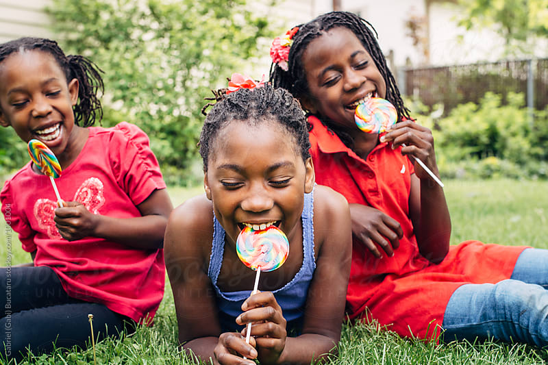 Three laughing black girls with lollipops by Gabriel (Gabi) Bucataru for Stocksy United