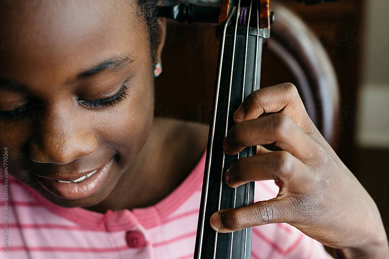 Smiling African American girl playing cello by Gabriel (Gabi) Bucataru for Stocksy United